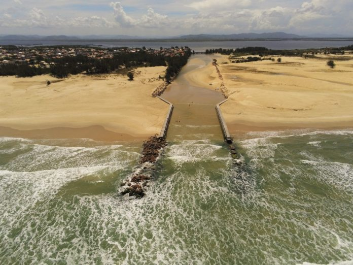 #Pracegover Na foto, vista aérea do encontro da lagoa com o mar