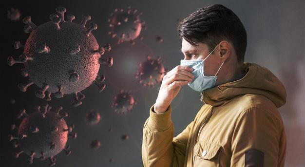 #Pracegover Na foto, homem com uma máscara, e ao fundo imagens de células do novo coranavírus