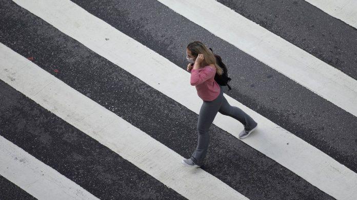 #Pracegover Na foto, mulher atravessa uma faixa de pedestre. Ela veste calça cinza, blusa rosa e está com máscara branca
