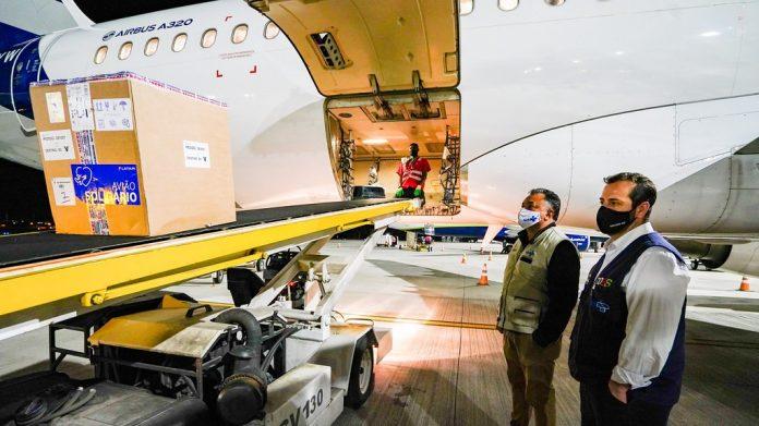 #Pracegover Na foto, caixas com a vacina sendo retirada do compartimento de bagagens de um avião
