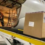 #Pracegover Na foto, caixa com vacinas sendo retiradas do compartimento de bagagem de um avião