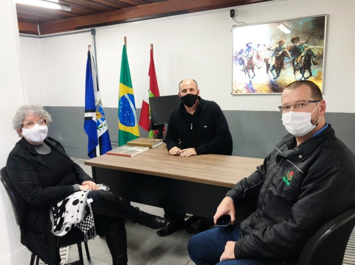 #Pacegover Foto: na imagem há três pessoas, dois homens e uma mulher , três bandeiras, três cadeiras e uma mesa
