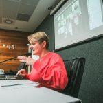 #Pracegover Foto: na imagem há uma mulher, uma cadeira, mesa, microfone