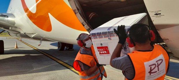 #Pracegover Foto: na imagem há dois homens, uma aeronave e uma caixa
