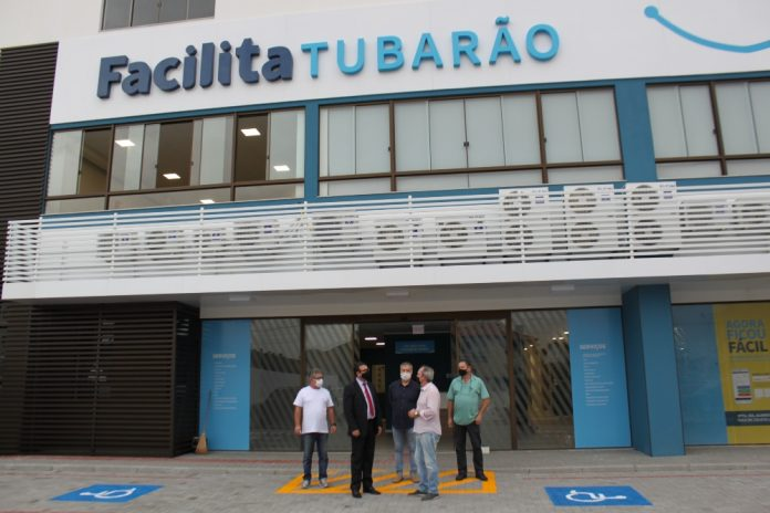 #Pracegover Na foto, pessoas em frente à fachada do Facilita Tubarão