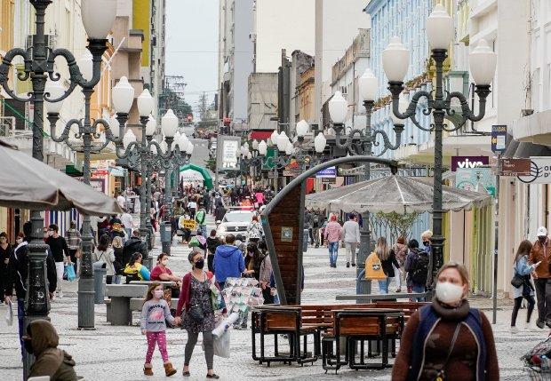 #Pracegover Foto: na imagem há pessoas, rua, bancos e lâmpadas