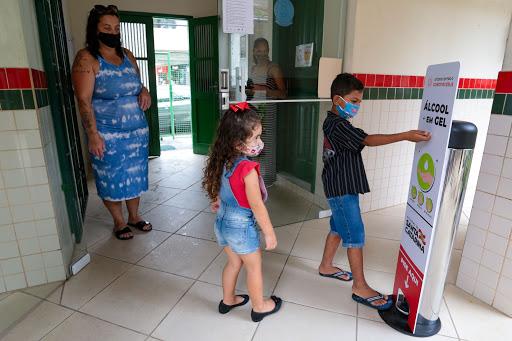#Pracegover Na foto, crianças usando máscara, higienizam as mãos antes de entrar na escola. Há duas profissionais aguardando na entrada
