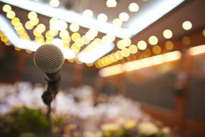 #Pracegover Na foto, um microfone sobre o palco, e ao fundo, imagem desfocada da plateia e luzes de teatro