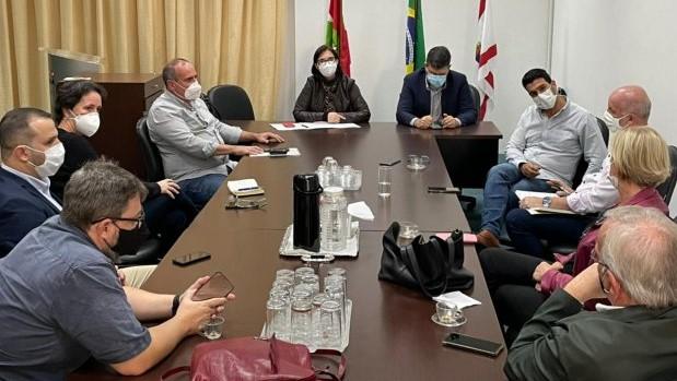 #Pracegover Na foto, pessoas em volta de uma mesa durante reunião. Todos usam máscara e mantém distância