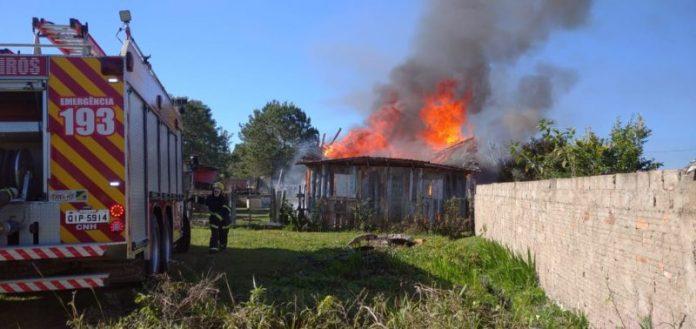 #Pracegover Foto: na imagem há um caminhão do Corpo de Bombeiros, uma casa em chamas, muro e uma área verde