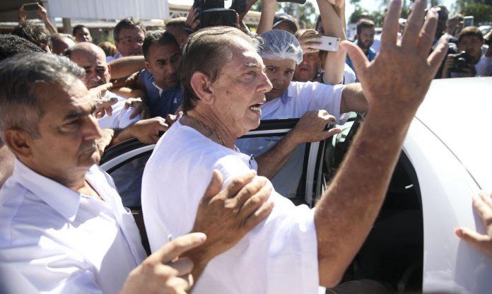 #Pracegover Na foto, João de Deus está entrando em um carro e rodeado de pessoas