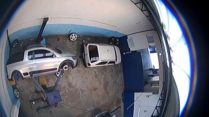 #Pracegover Na foto, carro aparece caído de lado, está dentro de uma oficina