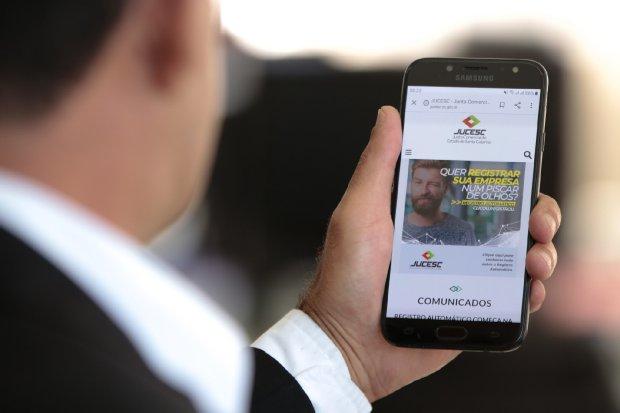 #Pracegover Foto: na imagem há um homem de terno e um celular