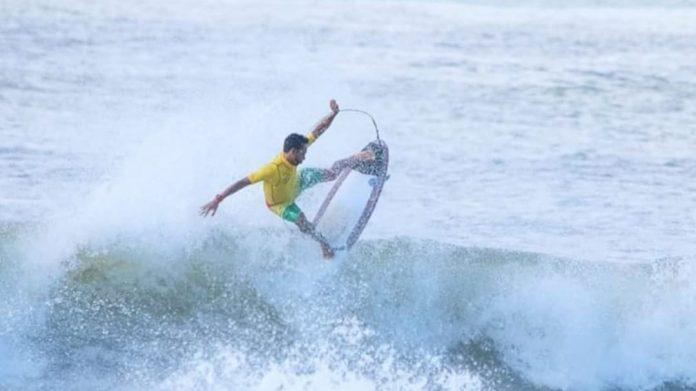 #Pracegover Na foto, um homem surfando em uma praia de Laguna