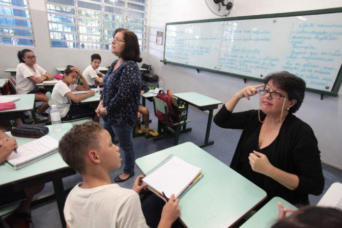 #Pracegover Na foto, mulher ensinando um aluno por meio de sinais