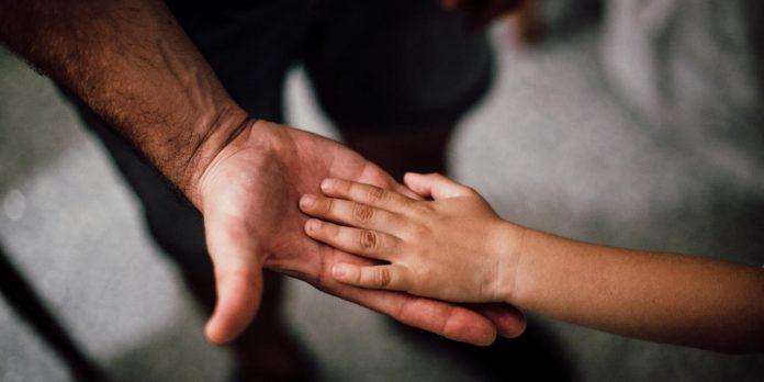 #Pracegover Foto: na imagem há duas mãos, uma de um adulto e a outra de uma criança