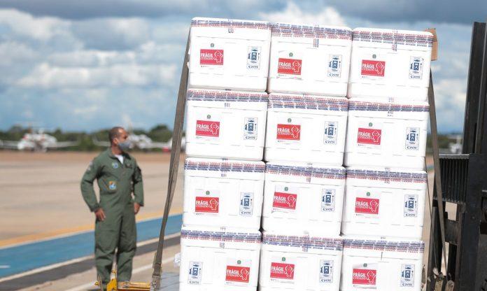 #Pracegover Na foto, aeroviário manuseando caixas de vacina