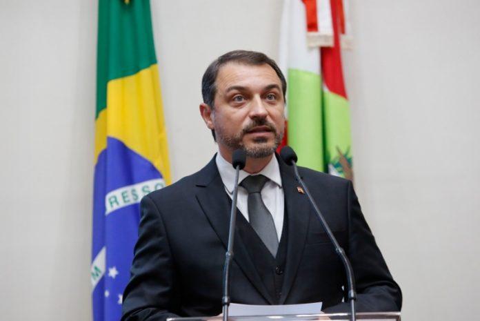 #Pracegover Foto: na imagem há um homem de terno, um microfone e duas bandeiras, a do país e do Estado de SC