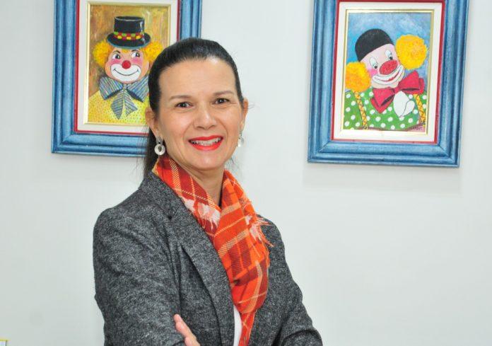 #Pracegover Foto: na imagem há uma mulher sorrindo e dois quadros