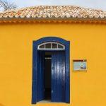 #Pracegover Na foto, fachada da casa de Anita, com paredes amarelas e janelas azul escuro