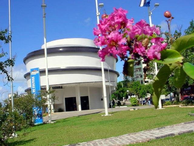 #Pracegover Foto: na imagem há uma edificação, gramado e flores