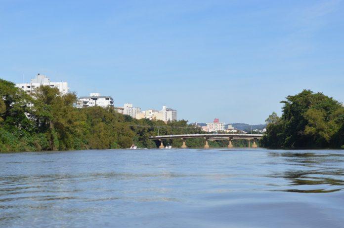 #Pracegover Na foto, destaque para águas calmas do rio, árvores nas margens e ao fundo uma ponte