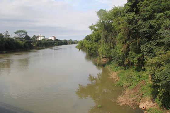 #Pracegover Na foto, rio com as águas calmas, mais escuras e árvores nas duas margens