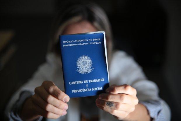 #Pracegover Na foto, uma mulher segurando uma carteira de trabalho