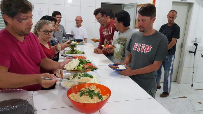 #Pracegover Na foto, pessoas em volta de uma mesa cheia de comida