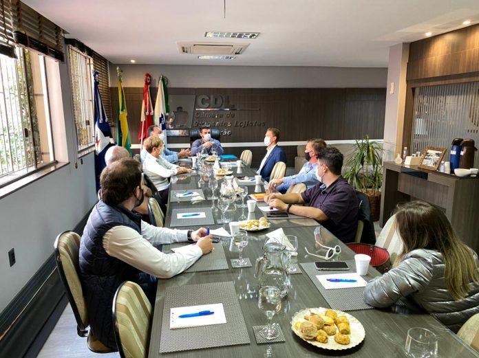 #Pracegover Na foto, pessoas em volta de uma mesa durante reunião