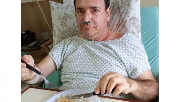 #Pracegover Na foto, Padre Edison aparece comendo e sentado em uma cama de hospital