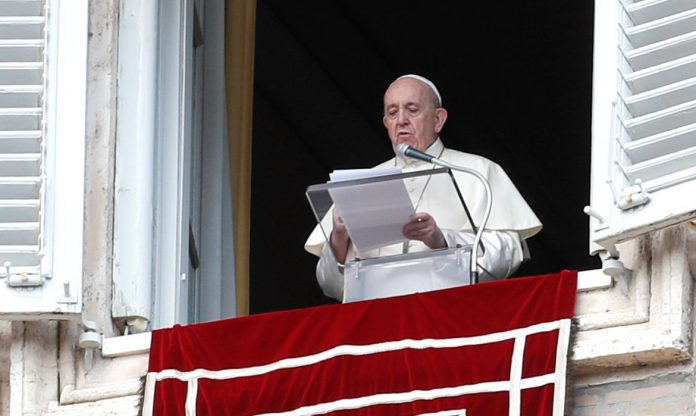 #Pracegover Foto: na imagem há uma janela, um homem e um tecido vermelho