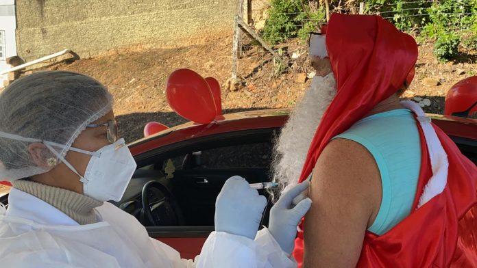 #Pracegover Na foto, profissional da saúde aplicando vacina em um homem vestido de Papai de Noel
