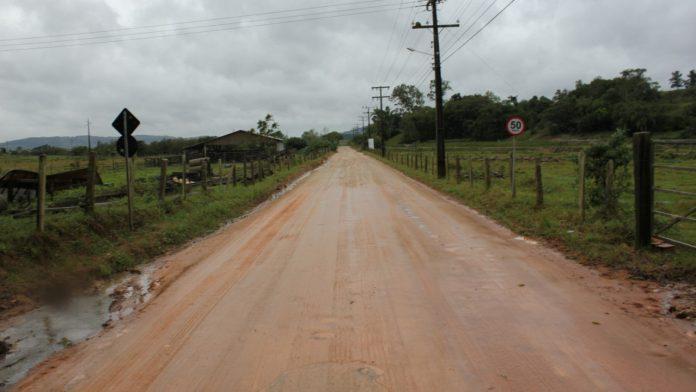 #Pracegover Na foto, estrada de chão, cercada por área verde