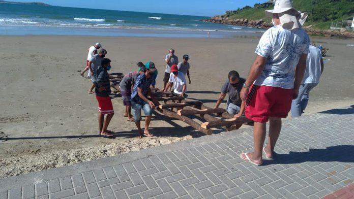 #Pracegover Na foto, pescadores preparam a rampa para a descida do barco na beira da praia