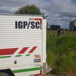 #Pracegover Na foto, carro do IGP no meio de um matagal e ao fundo policiais