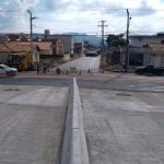 #Pracegover Foto: na imagem há uma ponte, máquina, casas e ruas