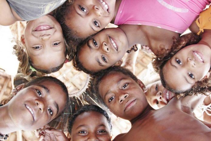#Pracegover Na foto, crianças abraçadas olhando para a câmera