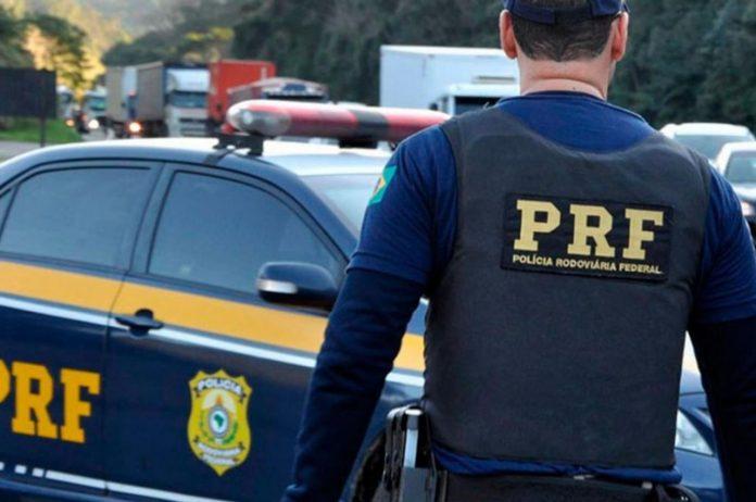 #Pracegover Foto: na imagem há um homem, um veículo da PRF, carros e caminhões