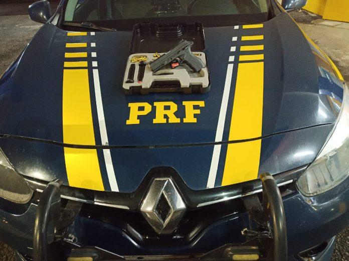 #Pracegover Foto: na imagem há um veículo da PRF e uma pistola