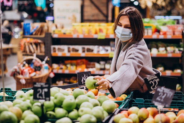#Pracegover Na foto, Mulher usando máscara e fazendo compras em um supermercado