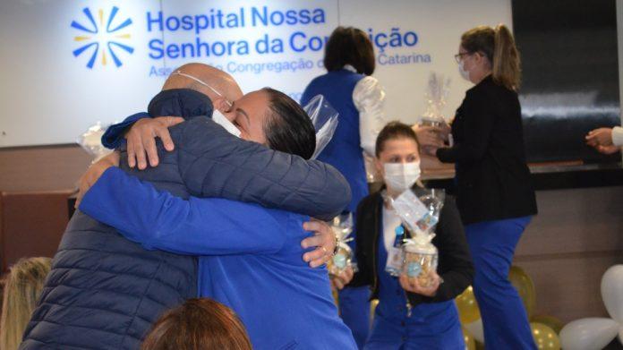 #Pracegover Na foto, duas um homem e uma mulher estão de máscara e se abraçam