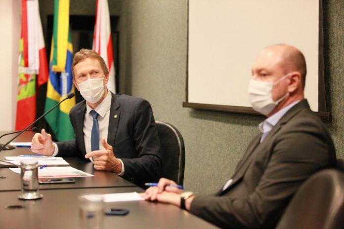 #Pracegover Foto: na imagem há dis homens, folhas, microfones e um copo de água