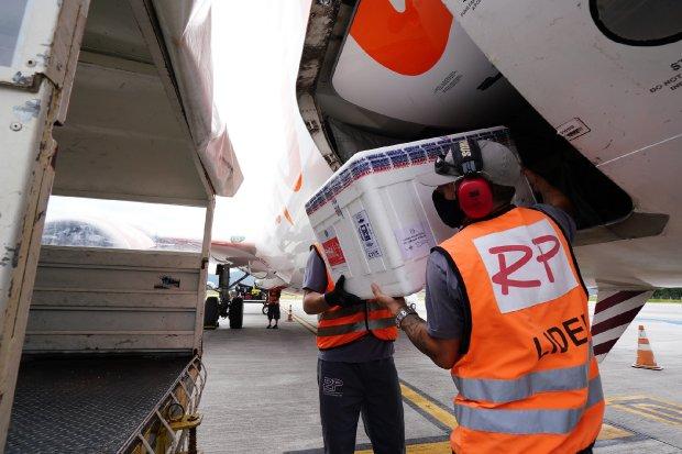 #Pracegover Na foto, homens retiram do compartimento de um avião caixas com doses de vacina
