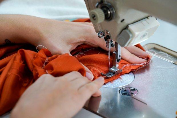 #Pracegover Na foto, mulher usando uma máquina para costurar tecido