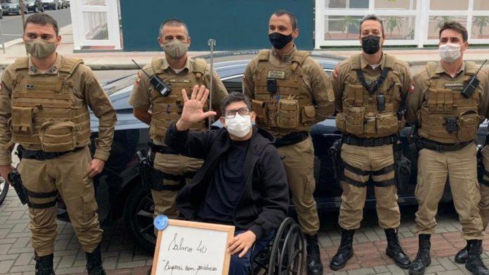 #Pracegover Na foto, homem sentado na cadeira de rodas e outros homens em pé atrás da cadeira