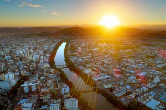 #Pracegover Na foto, imagem aérea da cidade com prédios, casas, rio no meio da cidade. Detalhe para o por do sol atrás do morro