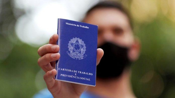 #Pracegover Na foto, uma pessoa segurando uma carteira de trabalho