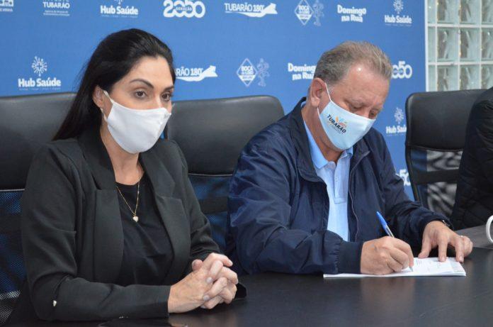 #Pracegover Foto: na imagem há um homem e uma mulher de máscaras, cadeiras, mesa, folha e caneta