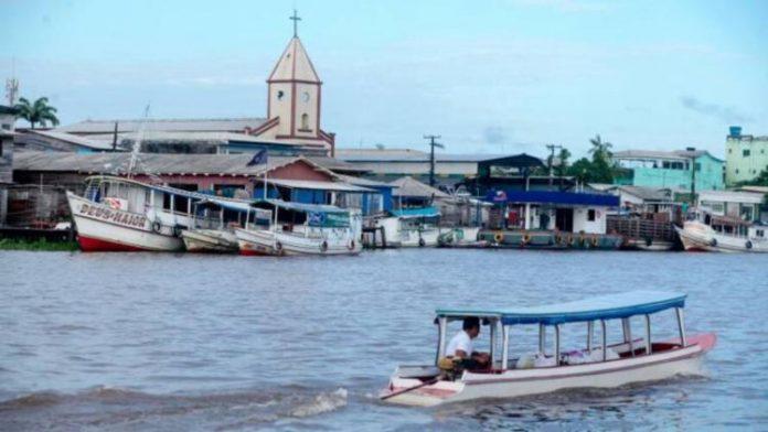 #Pracegover Foto: na imagem há um rio, barcos e uma igreja